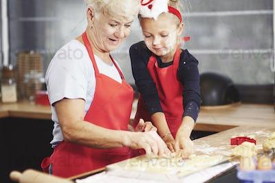 Cute girl with her grandma making dough