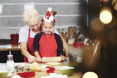 Grandmother teaching her granddaughter how to roll dough out
