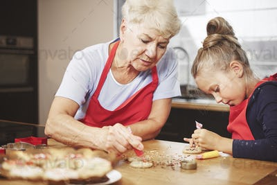 Grandma with girl baking and decorating cookies together