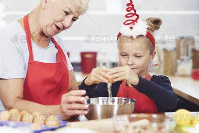 Grandma and granddaughter preparing snack in kitchen