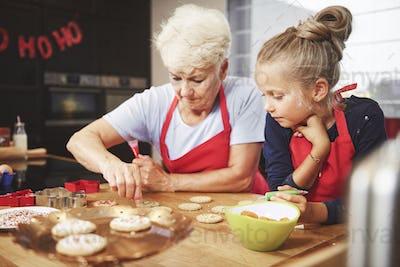Senior and girl preparing christmas cookies