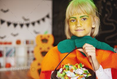 Girl in pumpkin costume with a bowl of candies