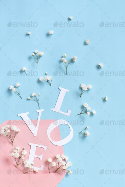 Flowers, pink envelope and word Love on a light blue background
