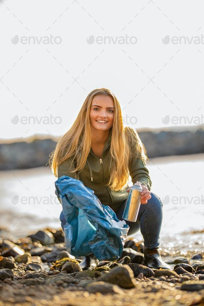 Young woman picking up aerosol can at beach
