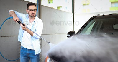 Person washing his car in carwashin jet with cleaner