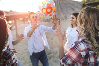 Group of young cheerful friends playing with ball