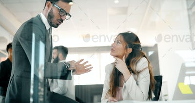 Picture of businessman and businesswoman talking in office