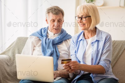 Mature couple shopping online in Internet, using laptop