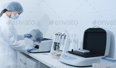 Young woman working in modern laboratory and using analyzer