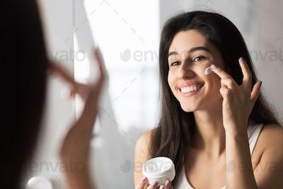 Cheerful Girl Applying Face Cream Looking In Mirror Indoor