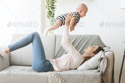 Mother lifting newborn baby in air while lying on sofa