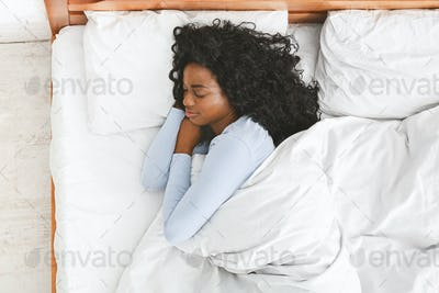 Rear view of young woman sleeping in her bed