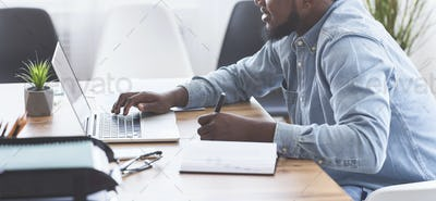 Black trainee taking notes while using laptop in office