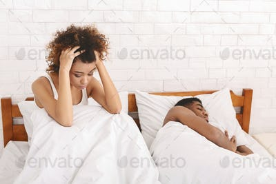 Stressed african american woman with insomnia sitting in bed