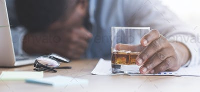 Drunk businessman sleeping at workplace with whiskey glass in hand