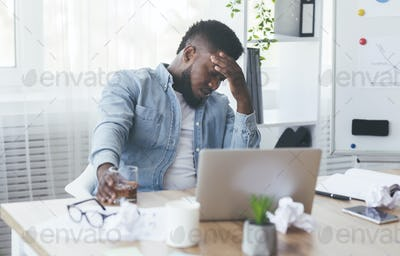 Depressed black businessman drinking alcohol at workplace in office