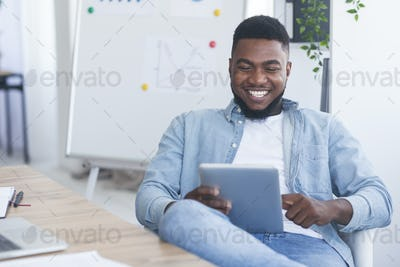 Cheerful african businessman sitting with digital tablet in modern office
