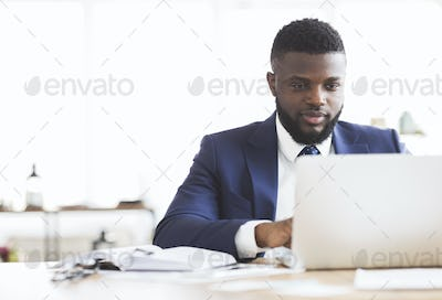 Concentrated businessman working with laptop in office
