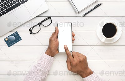 Black hands using smartphone with blank screen at workplace