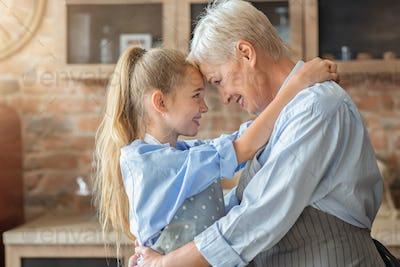 Little granddaughter hugging her happy grandmother in kitchen