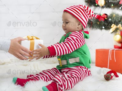 Adorable baby boy in elf costume getting Christmas gift