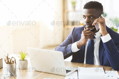 Young entrepreneur having conversation with business partner by cellphone