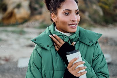 Pretty smiling African American girl in down jacket with cup to go happily looking away outdoor
