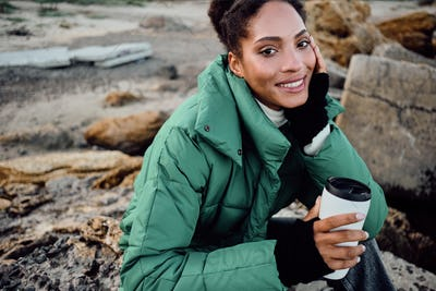 Smiling African American girl in down jacket with cup to go joyfully looking in camera outdoor