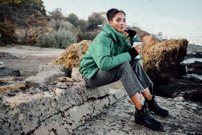 Beautiful African American girl in down jacket with cup to go happily sitting on rocks by the sea