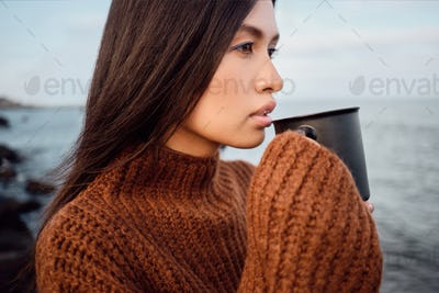 Pretty Asian brunette girl in knitted sweater with mug thoughtfully looking aside on seaside