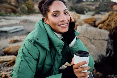 Attractive smiling African American girl in down jacket with cup to go happily looking in camera