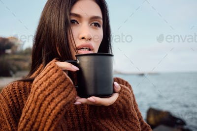Beautiful Asian brunette girl in knitted sweater with mug in hands sensually looking away on seaside