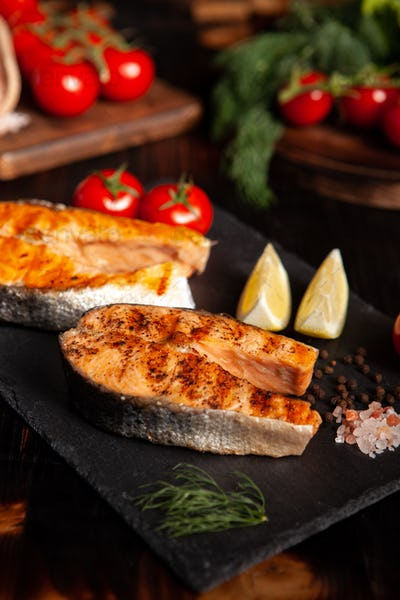 Cooked salmon rounds placed on a platter with a few slices of lime beside it