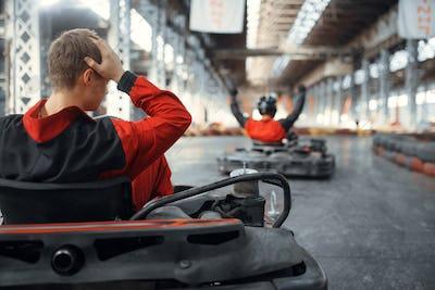 Two kart racers, winner and looser, karting