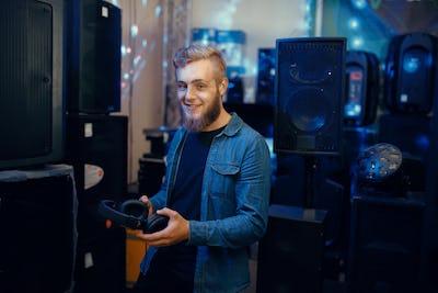 Young musician choosing headphones in music store