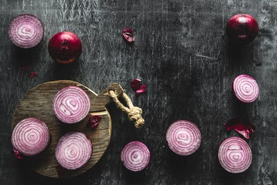 Red Onion Slices on wooden board with dark background. Wholesome healthy food