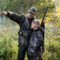 Father with gun showing something to son while hunting on a nature