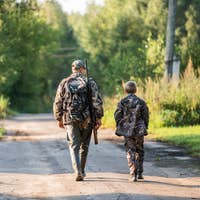 father pointing and guiding son on first deer hunt
