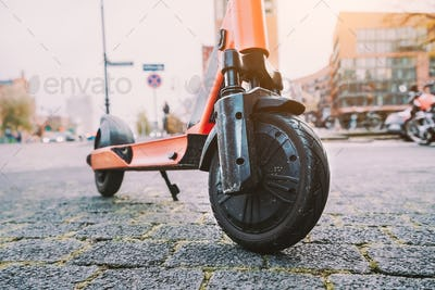 Lilac e-scooter front wheel tire perspective parked outdoor on pavement of urban city scene. Hamburg