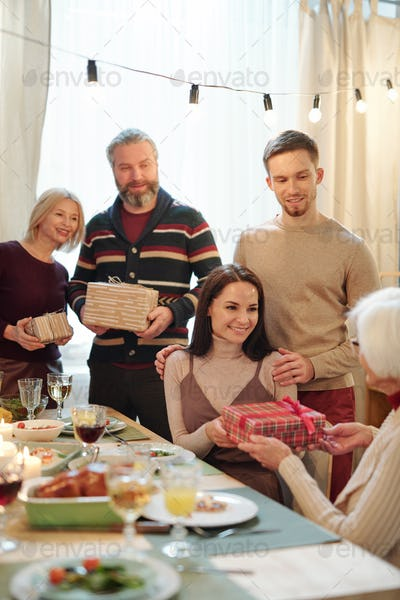 Young affectionate couple giving Christmas present in giftbox to granny by table