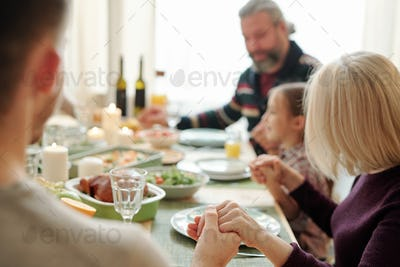 Young man, his mature mother and the rest of family holding by hands by table