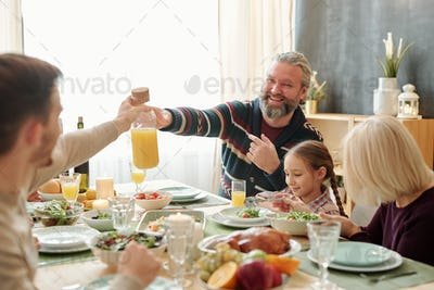 Happy senior man passing bottle of orange juice to his son over served table