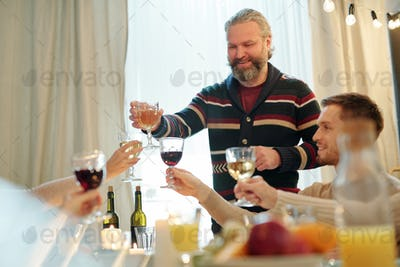 Smiling mature man clinking with glass of wine with other family members