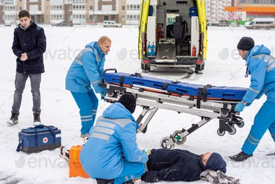 Brigade of young paramedics in workwear preparing stretcher for unconscious man