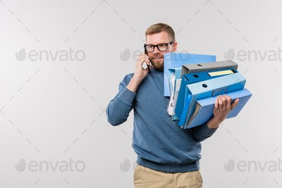 Busy young bearded manager with stack of folders holding smartphone by ear