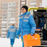 Young female paramedic with first aid kit while hurrying to sick person outdoors