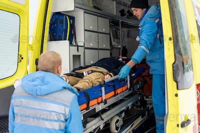 Paramedics in uniform pushing stretcher with unconscious man into ambulance car