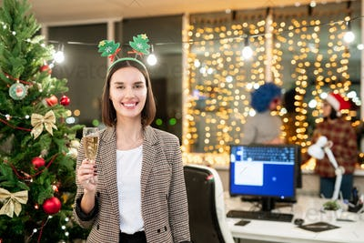 Cheerful office manager with flute of champagne toasting in front of camera