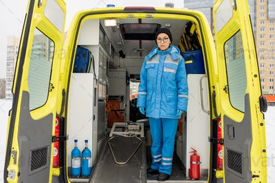 Young female paramedic in uniform standing by empty stretcher in ambulance car