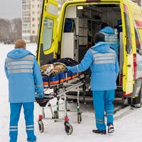 Paramedics pushing stretcher with fixed unconscious man into ambulance car
